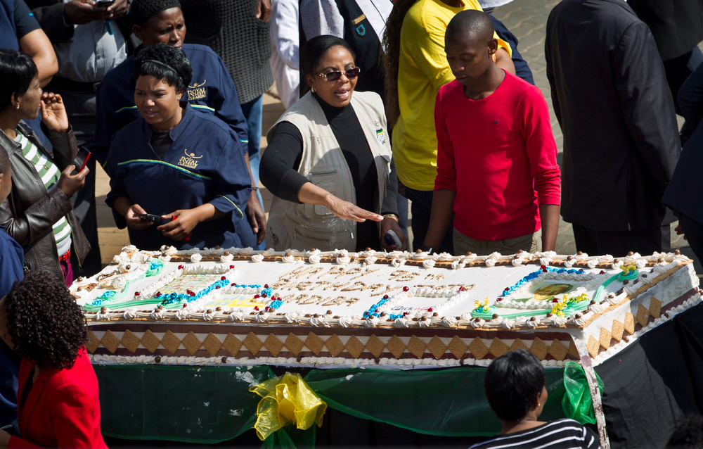 . Unidentified guests and hospital workers prepare to cut a large birthday cake for Nelson Mandela inside the gates of the Mediclinic Heart Hospital where former South African President Nelson Mandela is being treated in Pretoria, South Africa Thursday, July 18, 2013. South Africa celebrated Nelson Mandela\'s 95th birthday on Thursday, a milestone capped by news that the former president\'s health was improving after fears that he was close to death during ongoing hospital treatment. (AP Photo/Ben Curtis)