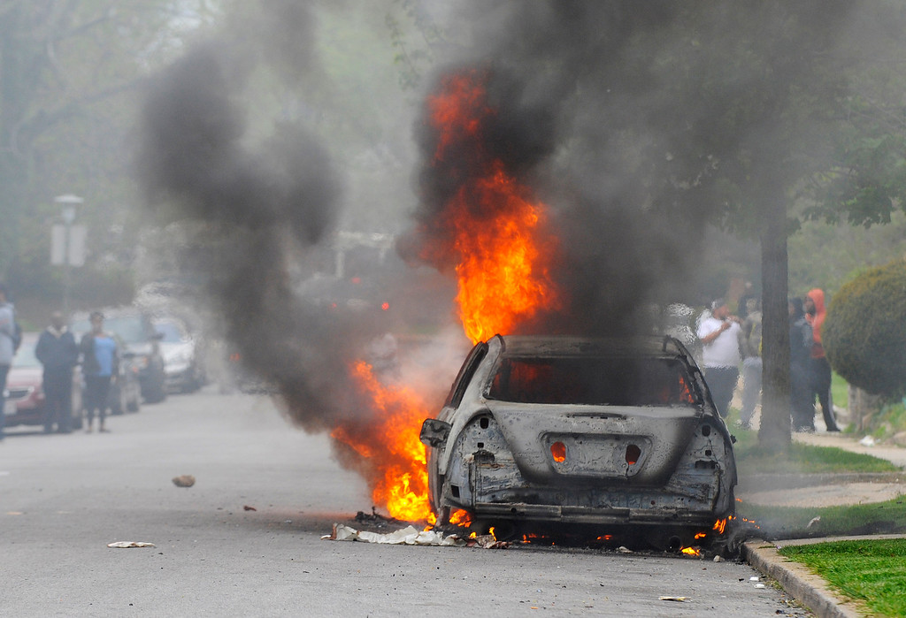 . A car burns Monday, April 27, 2015, during unrest following the funeral of Freddie Gray in Baltimore. (Lloyd Fox/The Baltimore Sun via AP)