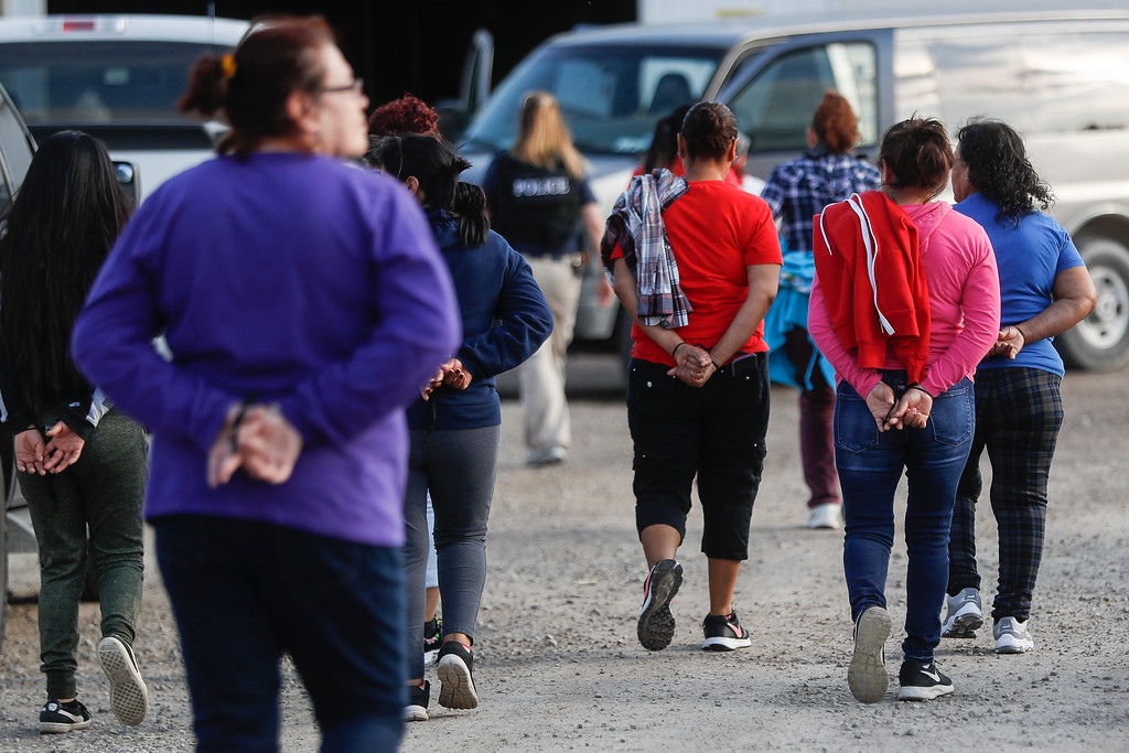 . Government agents lead suspects in custody towards a restroom during an immigration sting at Corso\'s Flower and Garden Center, Tuesday, June 5, 2018, in Castalia, Ohio. The operation is one of the largest against employers in recent years on allegations of violating immigration laws. (AP Photo/John Minchillo)
