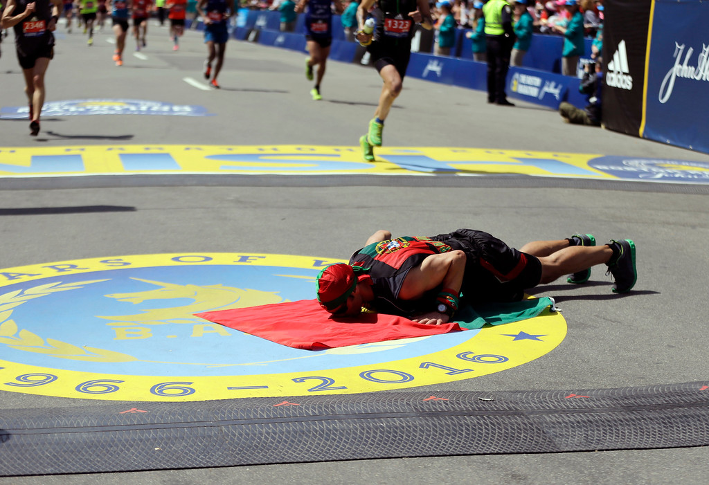 . Manuel Cabral, of Canada, kisses a flag of Portugal after finishing the 120th Boston Marathon on Monday, April 18, 2016, in Boston. (AP Photo/Elise Amendola)