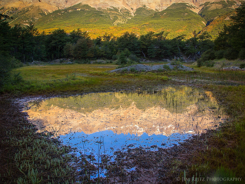 Distant mountains reflected in a small pond in Patagonia.