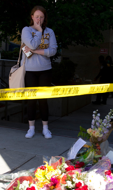 . An unidentified mourner stands by a makeshift shrine at the scene on Kittredge Street, where a balcony collapsed, sending 13 people plunging to the street below, Tuesday, June 16, 2015, in Berkeley, Calif. Six people were killed and seven more were transported to area hospitals. (D. Ross Cameron/Bay Area News Group)