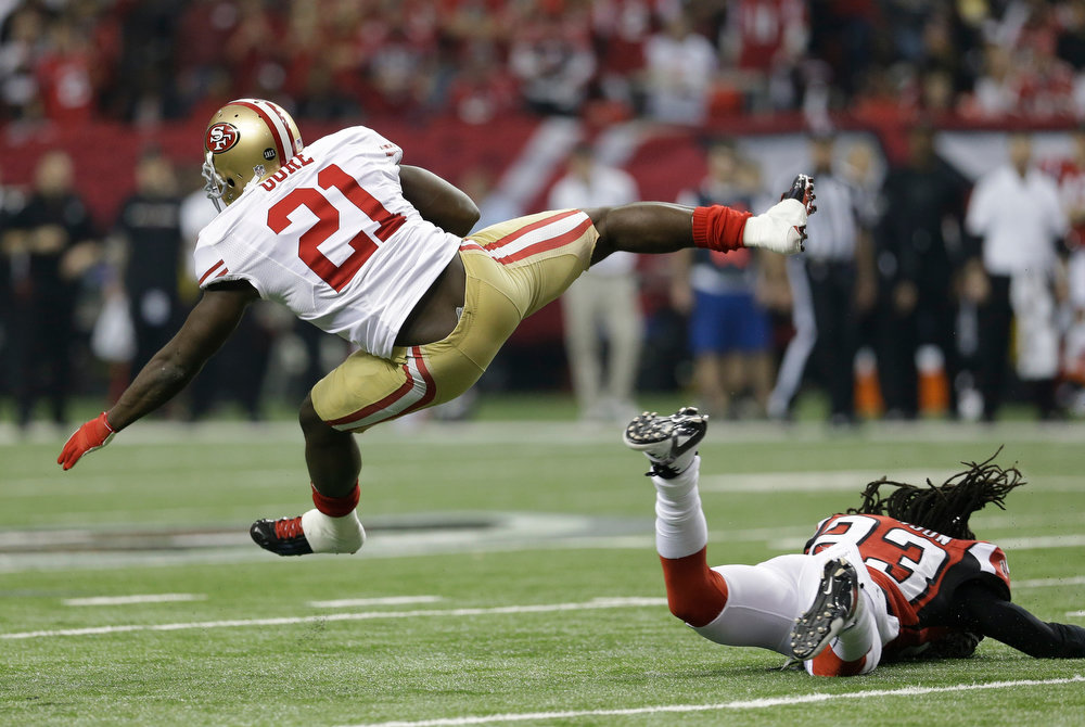 Description of . San Francisco 49ers\' Frank Gore gets past Atlanta Falcons\' Dunta Robinson (23) for a first down during the first half of the NFL football NFC Championship game Sunday, Jan. 20, 2013, in Atlanta. (AP Photo/Mark Humphrey)