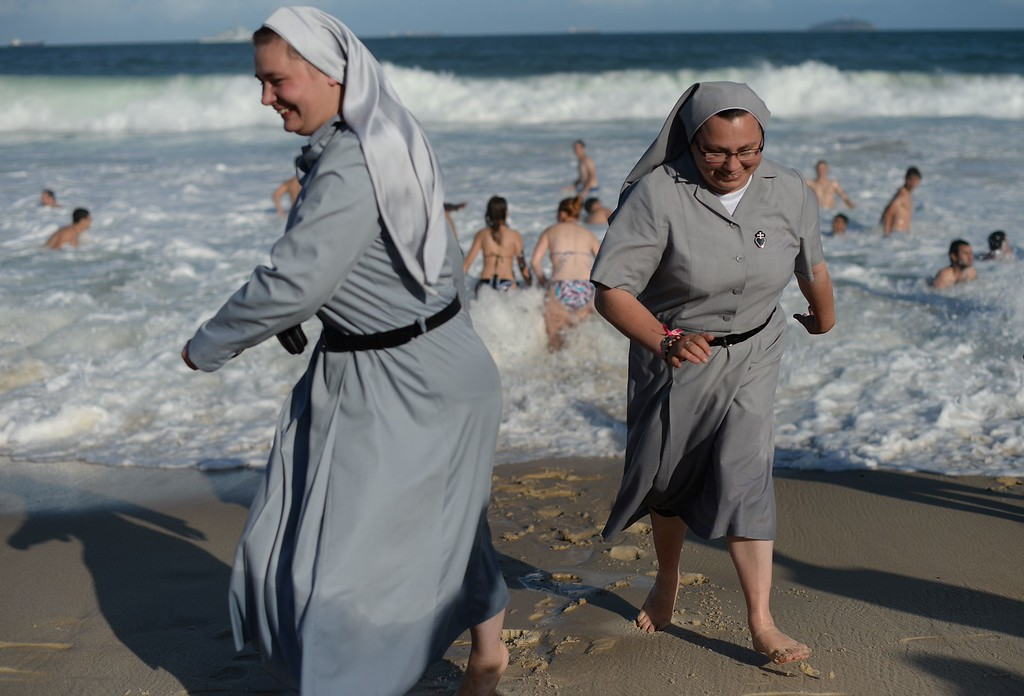 ". Two Polish nuns laugh on the shore as hundreds of thousands of young Catholic pilgrims attending World Youth Day (WYD) start gathering at Copacabana beach in Rio de Janeiro for a prayer vigil with Pope Francis, on July 27, 2013. In a speech to Brazil\'s political, religious and civil society leaders earlier, Pope Francis said a ""constructive dialogue\"" was needed to confront the country\'s social turmoil, referring to the massive street protests that rocked Brazil last month to demand an end to corruption and better public services. YASUYOSHI CHIBA/AFP/Getty Images"