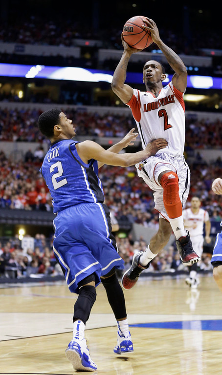 . Louisville guard Russ Smith (2) goes up with a shot past Duke guard Quinn Cook (2) during the first half of the Midwest Regional final in the NCAA college basketball tournament, Sunday, March 31, 2013, in Indianapolis. (AP Photo/Michael Conroy)