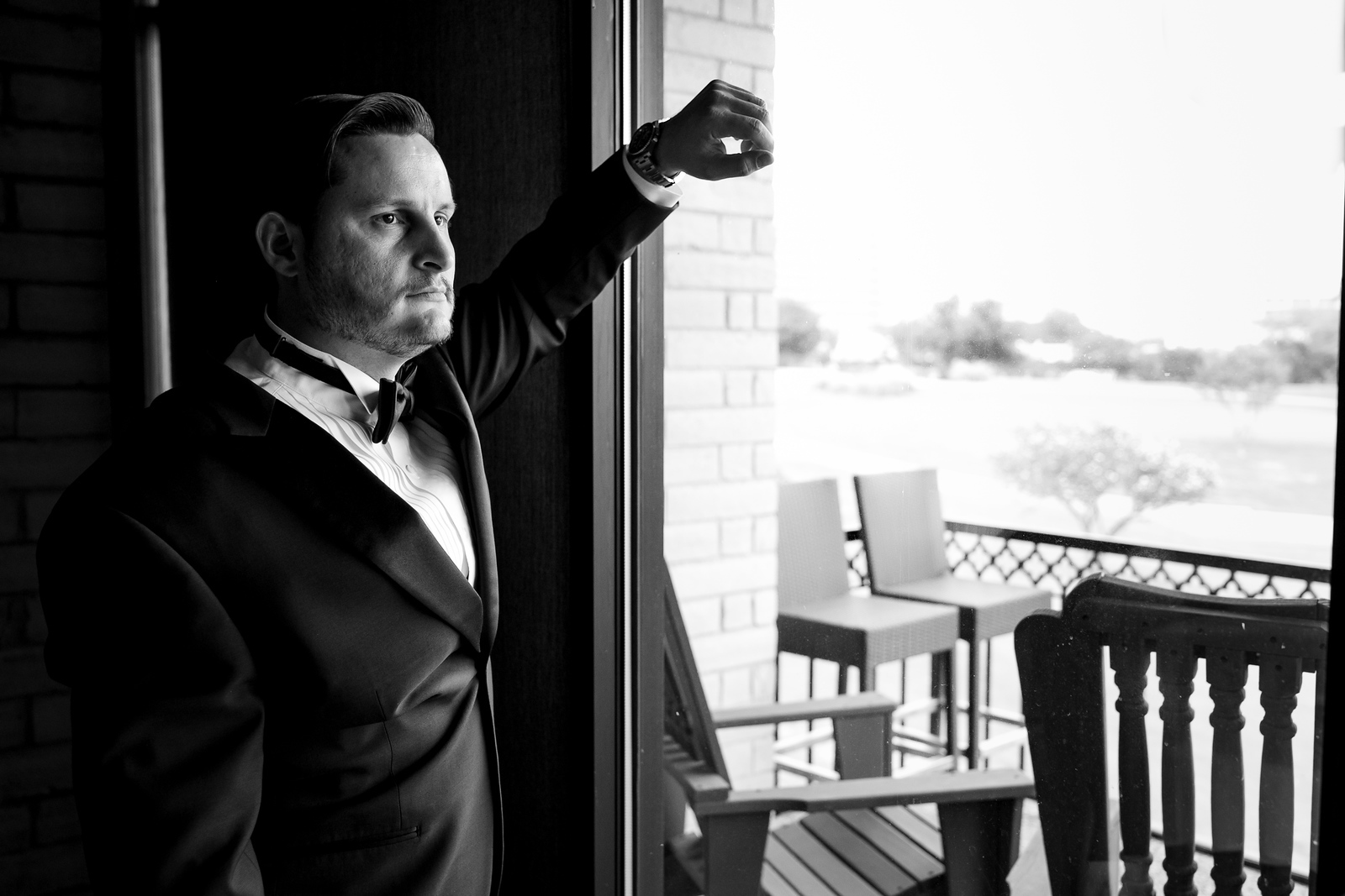 black and white photo of  a groom in a tuxedo staring out a window before his wedding day