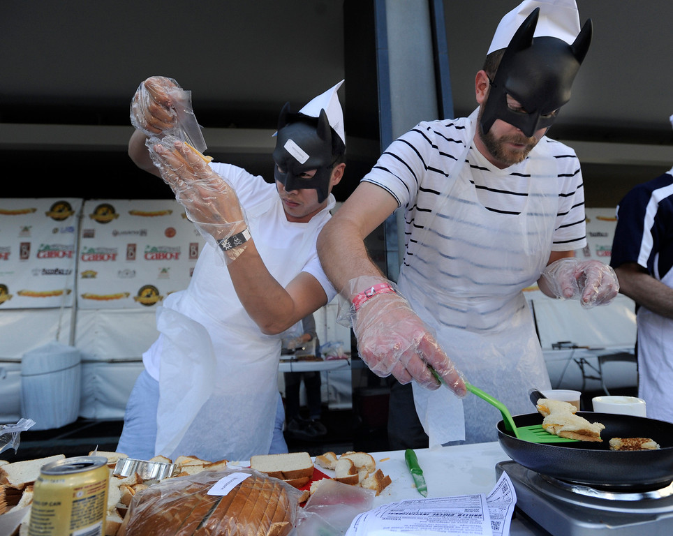 . (l-r) Andrew Bui and Taylor Henderson, wearing Batman masks for no apparent reason, cook up grilled cheese sandwiches in the shape of a goat. The 11th Annual Grilled Cheese Invitational was held Saturday at the Los Angeles Center Studios, 1201 W. 5th Street, in downtown. Cheese lovers came together to sample grilled cheese sandwiches in a variety of incarnations. Los Angeles, CA 4/20/2013(John McCoy/Staff Photographer