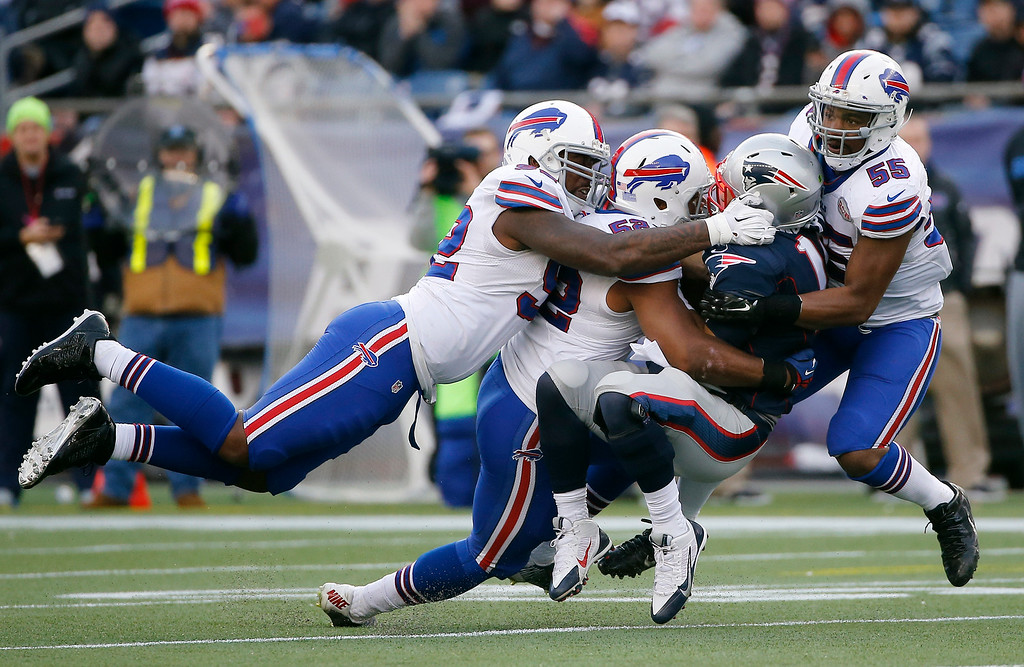 . Buffalo Bills defenders Jarius Wynn, left, Preston Brown, second from left, and Jerry Hughes, right, sack New England Patriots quarterback Jimmy Garoppolo in the second half of an NFL football game Sunday, Dec. 28, 2014, in Foxborough, Mass. The play was negated because of a penalty. (AP Photo/Elise Amendola)