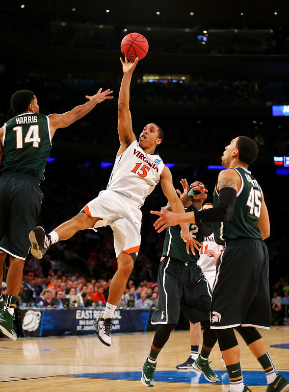. Malcolm Brogdon #15 of the Virginia Cavaliers goes up to shoot against Gary Harris #14 of the Michigan State Spartans during the regional semifinal of the 2014 NCAA Men\'s Basketball Tournament at Madison Square Garden on March 28, 2014 in New York City.  (Photo by Elsa/Getty Images)
