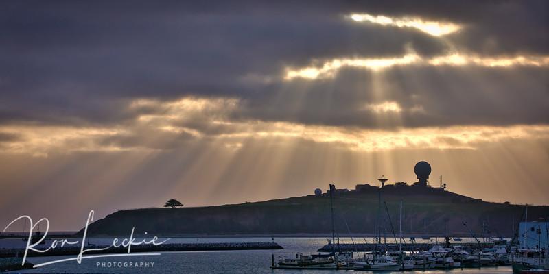 Sunrays over Half Moon Bay harbor