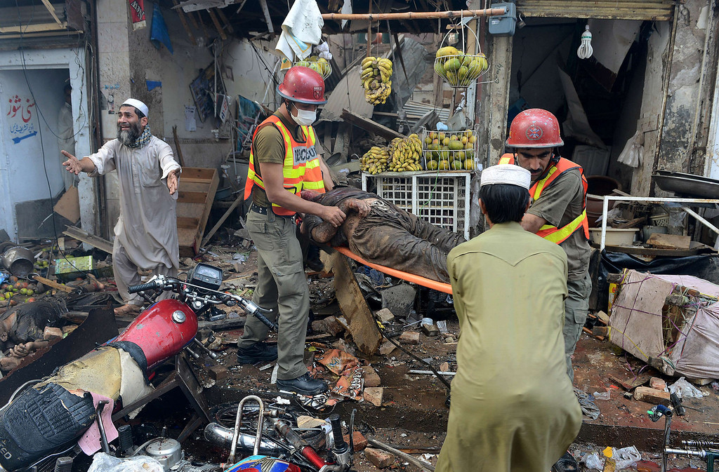. Pakistani volunteers carry a blast victim at the site of a bomb explosion in the busy Kissa Khwani market in Peshawar on September 29, 2013.  AFP PHOTO / A.  MAJEED/AFP/Getty Images