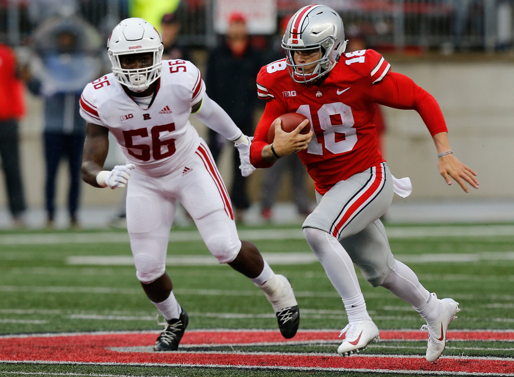 . Ohio State quarterback Tate Martell, right, runs past Rutgers linebacker Rashawn Battle to score a touchdown during the during the second half of an NCAA college football game Saturday, Sept. 8, 2018, in Columbus, Ohio. Ohio State beat Rutgers 52-3. (AP Photo/Jay LaPrete)