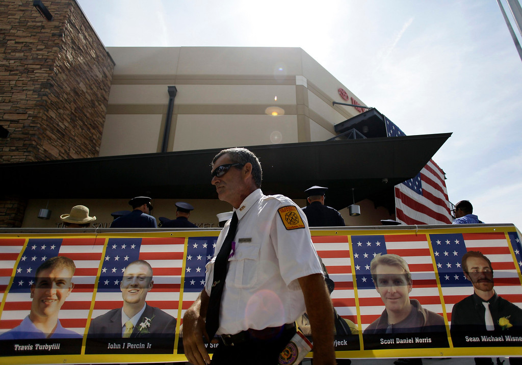 . A firefighter walks past a banner showing some of the faces of the Prescott Fire Department\'s Granite Mountain Interagency Hot Shot Crew during a memorial in Prescott Valley, Arizona July 9, 2013. REUTERS/Joshua Lott