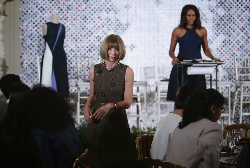 . Anna Wintour (L), Editor-in-Chief of Vogue magazine, steps off the stage after she introduced U.S. first lady Michelle Obama (R) during a session of a Fashion Education Workshop, hosted by the first lady, in the East Room of the White House October 8, 2014 in Washington, DC. (Photo by Alex Wong/Getty Images)