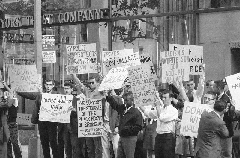 ". A group of young men hold up placards denouncing Alabama Governor George C. Wallace as he appeared on NBC\'s ""Meet the Press\"" television program in New York on June 2, 1963. The youths, members of so called \""Youth Against War and Fascism,\"" were demonstrating near NBC studios in New York\'s Rockefeller Center. Gov. Wallace said he opposed the enrollment of two African Americans at the University of Alabama. (AP Photo)"
