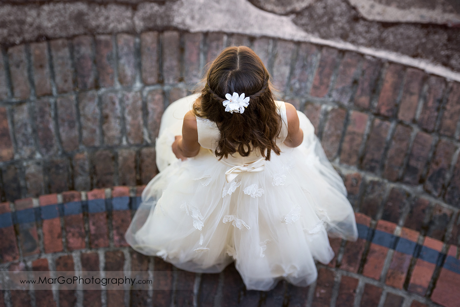 high angle of first communion girl in white dress showing back of the dress at Cafe Wisteria in Menlo Park