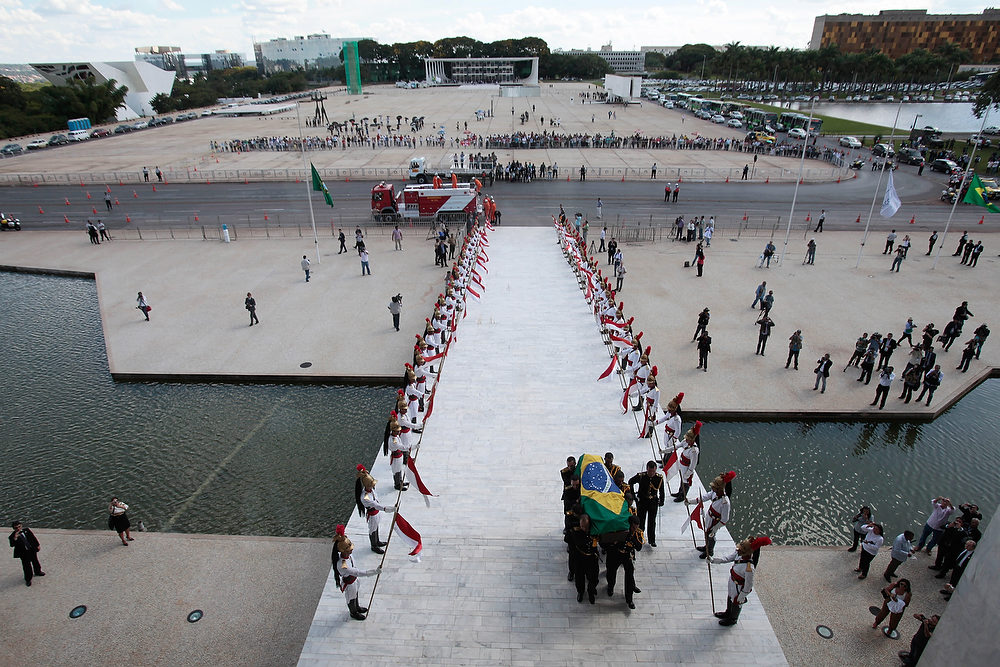 Description of . The flag-draped coffin containing the remains of Brazilian architect Oscar Niemeyer is carried past an honor and towards the entrance of the Planalto presidential palace, in Brasilia, Brazil, Thursday, Dec. 6, 2012. Niemeyer, 104, the groundbreaking architect who designed Brazil's futuristic capital and much of the United Nations complex, died Wednesday night in Rio de Janeiro, the seaside city where he was born and where his remains will be buried after he is honored with a service in Brasilia at the presidential palace he designed. (AP Photo/Eraldo Peres)