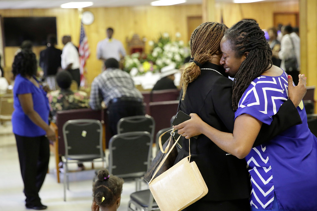 . Waltrina Middleton, right, cousin of shooting victim DePayne Doctor, embraces Claudia Lawton, Sunday, June 21, 2015, in Charleston, S.C., in the room in the basement where a mass shooting occurred at the Emanuel A.M.E. Church four days ago. The congregation at Emanuel African Methodist Episcopal swayed and sang, prayed and welcomed the world into their sanctuary on Sunday, holding the first worship service since a white gunman was accused of opening fire during a Bible study group, killing nine black church members. (AP Photo/David Goldman, Pool)