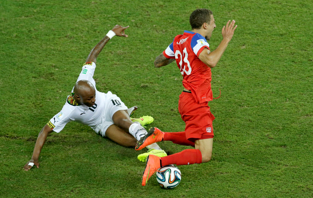 Description of . Ghana's Andre Ayew, left, fouls United States' Fabian Johnson during the group G World Cup soccer match between Ghana and the United States at the Arena das Dunas in Natal, Brazil, Monday, June 16, 2014. (AP Photo/Hassan Ammar)