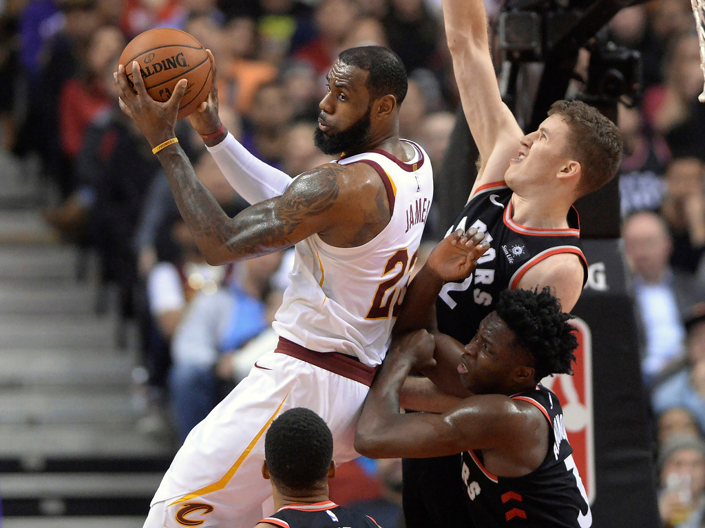 . Cleveland Cavaliers forward LeBron James (23) grabs a rebound in front of Toronto Raptors center Jakob Poeltl (42) and forward OG Anunoby (3) during the first half of an NBA basketball game Thursday, Jan. 11, 2018, in Toronto. (Frank Gunn/The Canadian Press via AP)