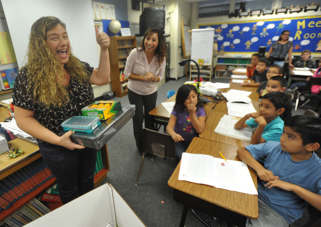 . OfficeMax representatives surprise second grade teacher Natalia Weberg, left, with $1,200 worth of classroom supplies and resources at Ceres Elementary School in Whittier on Wednesday October 2, 2013. Principal Julie Gonzalez nominated the second grade teacher for the Adopt a Classroom grant sponsored by Office Max and Adopt a Classroom. (Whittier Daily News/Staff Photo by Keith Durflinger)