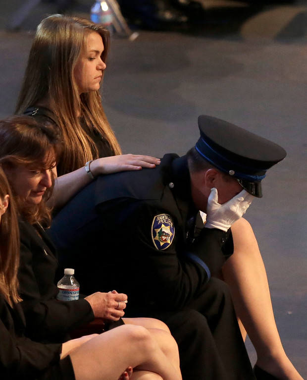 ". Santa Cruz police officer Adam Baker weeps during a memorial service for his father, Sgt. Loran ""Butch\"" Baker, Thursday, March 7, 2013, at HP Pavilion in San Jose, Calif. Sgt. Baker and detective Elizabeth Butler were shot to death on Feb. 26, after arriving at the home of Jeremy Peter Goulet to question him about a misdemeanor sexual assault. (AP Photo/Ben Margot)"