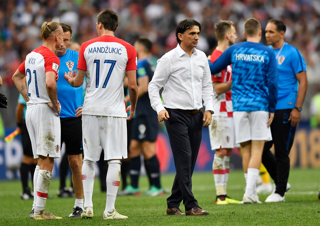 . Croatia head coach Zlatko Dalic, center, comforts his players after losing 2-4 during the final match between France and Croatia at the 2018 soccer World Cup in the Luzhniki Stadium in Moscow, Russia, Sunday, July 15, 2018. (AP Photo/Martin Meissner)