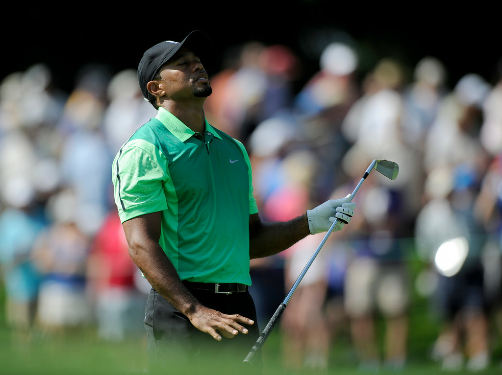 . Tiger Woods reacts on the 17th fairway during the first round of the Quicken Loans National golf tournament, Thursday, June 26, 2014, in Bethesda, Md. (AP Photo/Nick Wass)