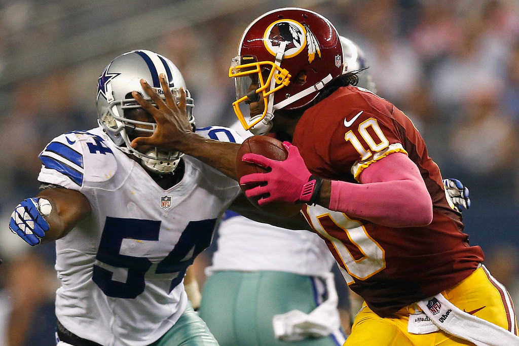 . ARLINGTON, TX - OCTOBER 13:   Robert Griffin III #10 of the Washington Redskins scrambles with the ball against  Bruce Carter #54 of the Dallas Cowboys on October 13, 2013 in Arlington, Texas. The Cowboys beat the Redskins 31-16. (Photo by Tom Pennington/Getty Images)