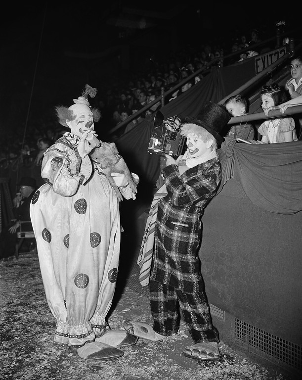". Kenneth Lucas, clown photographer, takes a picture of Felix Adler, ""The King of Clowns,\"" at the Ringling Bros. and Barnum & Bailey Circus in New York, May 2, 1944. Adler feeds a piglet with a bottle to the delight of the children in the audience. (AP Photo/Charles Kenneth Lucas)"