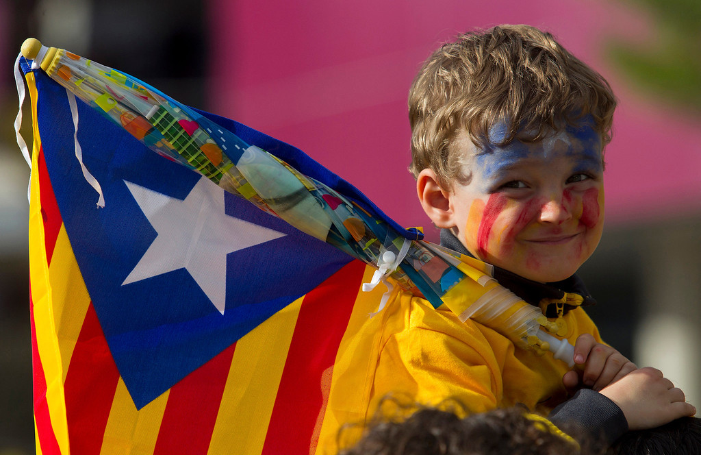 . A young boy holding an Independentist Catala flag (Senyera) smiles as Catalans gather in a bid to create a 400-kilometre (250-mile) human chain, part of a campaign for independence from Spain during Catalonia National Day, or Diada, outside the FC Barcelona\'s Camp Nou stadium in Barcelona, on September 11, 2013. Independence-seeking Catalans  marshaled their forces today to make a human link they say will stretch across 86 cities, towns and villages along the coast of the northeastern region on the Mediterranean, passing landmarks such as the Sagrada Familia basilica in Barcelona and the city\'s Camp Nou football stadium. QUIQUE GARCIA/AFP/Getty Images