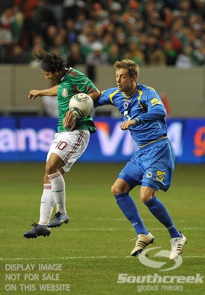 Mexico's Forward Giovani Dos Santos (#10) and Bosnia-Herzegovina's Defender Adnan Mravac (#5) fight for the ball in Soccer action between Bosnia-Herzegovina and Mexico.  Mexico defeated Bosnia-Herzegovina 2-0 in the game at the Georgia Dome in Atlanta, GA.
