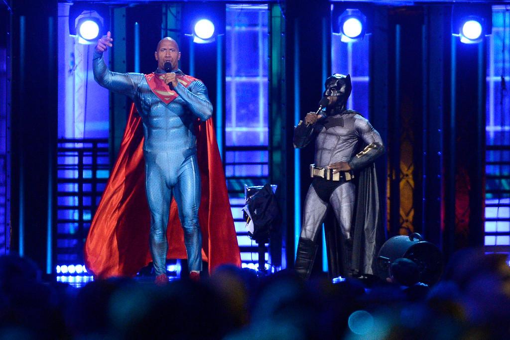 . Kevin Hart, dressed as Batman, and Dwayne Johnson, dressed as Superman, speak at the MTV Movie Awards at Warner Bros. Studio on Saturday, April 9, 2016, in Burbank, Calif. (Kevork Djansezian/Pool Photo via AP)
