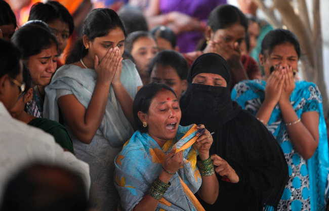 Description of . Relatives and neighbors mourn by the body of Swapna Reddy, killed in Thursdayís explosion, at their house in Hyderabad, India, Friday, Feb. 22, 2013. A day after two bicycle bombs killed more than a dozen people and wounded more than 100, investigators into India's worst bombing in more than a year searched Friday for possible links to anger over the execution of a Muslim militant. (AP Photo/ Mahesh Kumar A.)