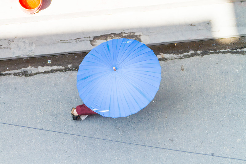 A shot from above of a woman walking with a blue umbrella through the streets of Kathmandu's Thamel District.