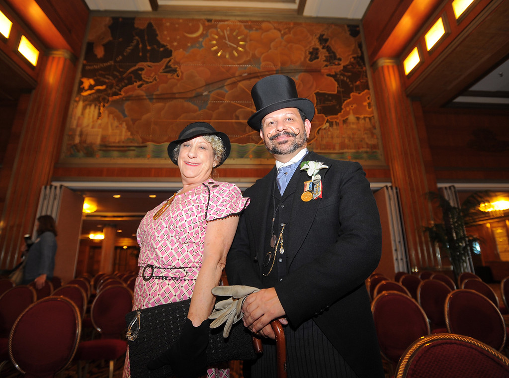 . Marcy Downes and Michael Ontiveros dress in period clothes to celebrate with the Queen Mary on its 80th anniversary of her launching in Long Beach, CA on Friday, September 26, 2014. After some speeches and a short film, guests were able to sample a slice of cake from a 15-foot long, 600-pound replica of the ship made by baker Jose Barajas. (Photo by Scott Varley, Daily Breeze)