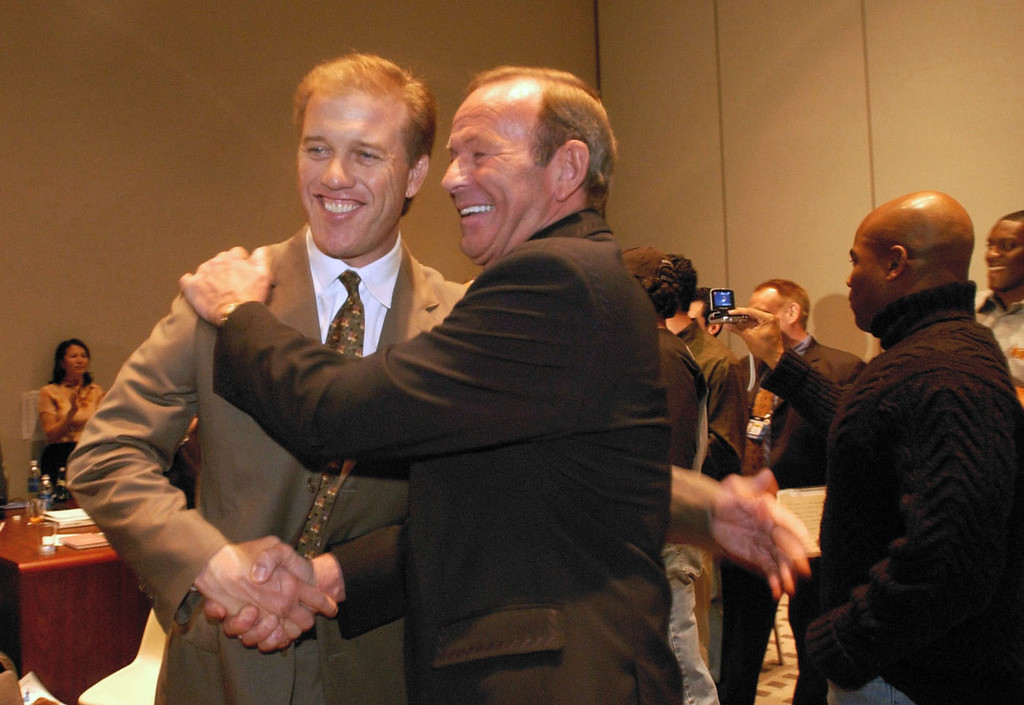 . Broncos Owner Pat Bowlen shakes hands and hugs John Elway congratulating him on becoming the first Denver Broncos player to be inducted to the Pro Football Hall of Fame. The enshrinement of the Class of 2004 will take place at the Pro Football Hall of Fame in Canton, on Sunday, August 8, 2004. (DENVER POST PHOTO BY JOHN LEYBA)