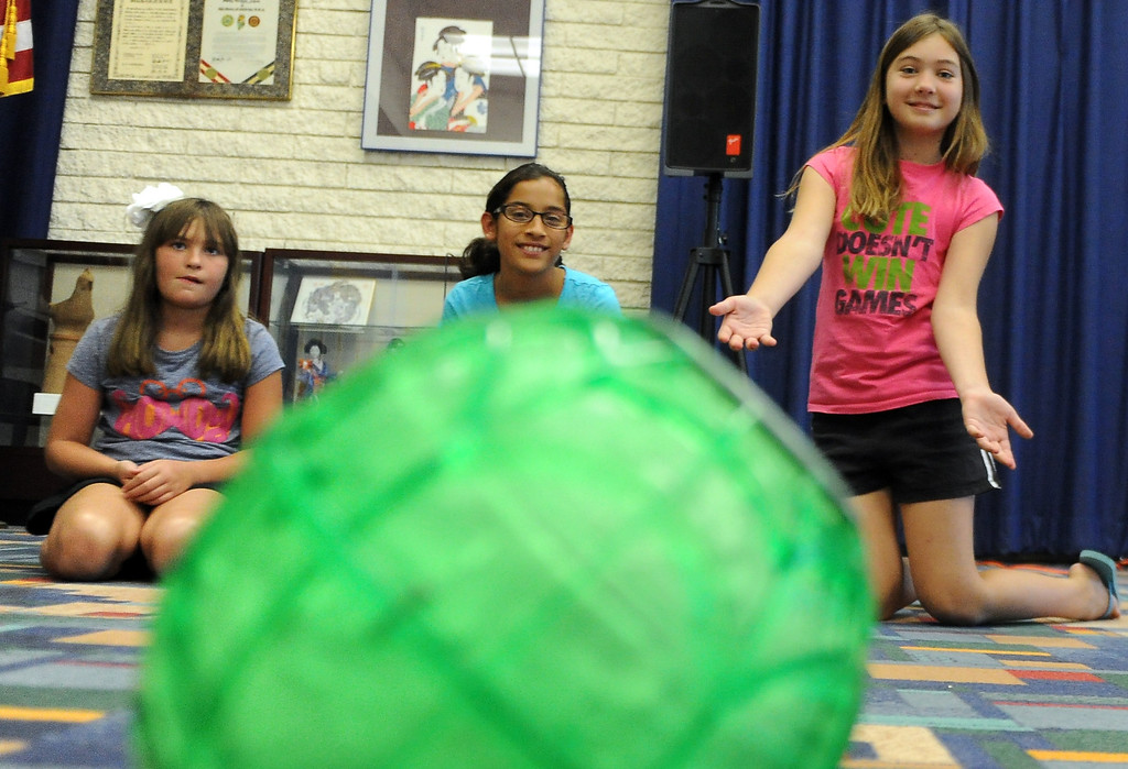 . Ten year-old Kayla Scoria, right, rolls the ice cream ball during a Summer Teen Reading Club ice-cream making and tasting session at the Glendora Public Library Bidwell Forum on Wednesday, July 17, 2013 in Glendora, Calif. 