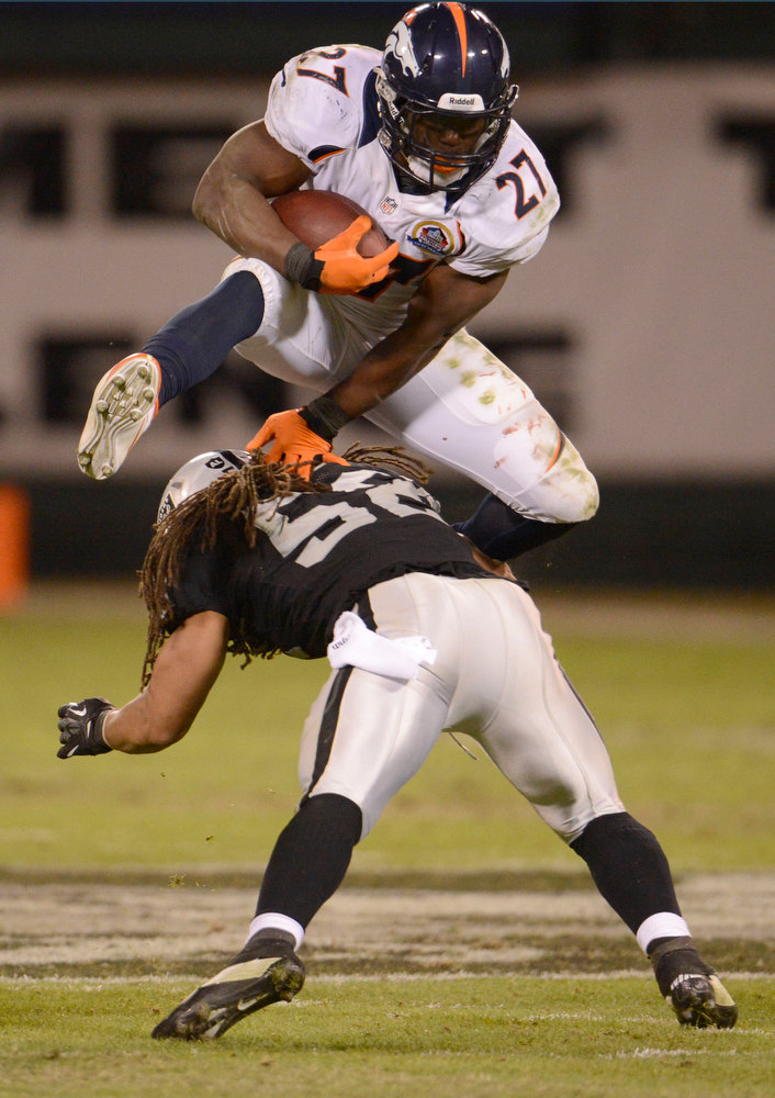 . Denver Broncos running back Knowshon Moreno (27) hurdles Oakland Raiders outside linebacker Philip Wheeler (52) to pick up a some yards during the third quarter Thursday, December 6, 2012 during Thursday Night Football at O.c Coliseum in Oakland  John Leyba, The Denver Post