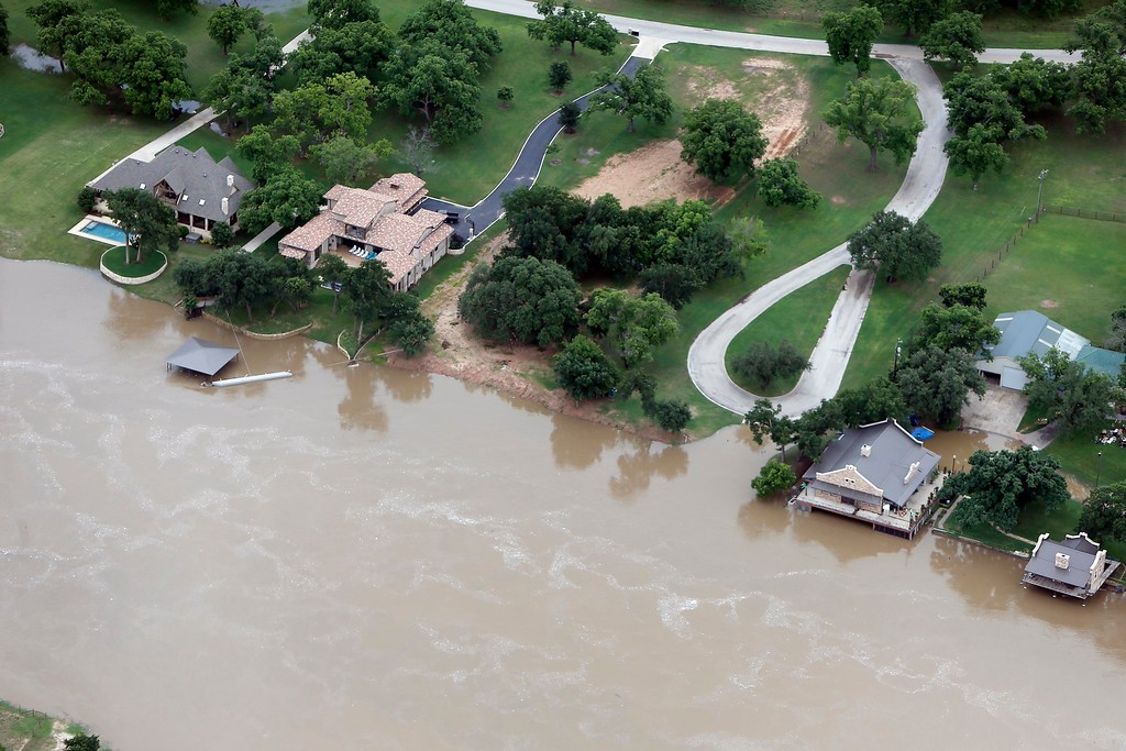 . Flood waters from the Brazos River encroach upon homes in the Horseshoe Bend neighborhood, Friday, May 29, 2015, in Weatherford, Texas. Floodwaters submerged Texas highways and threatened more homes Friday after another round of heavy rain added to the damage inflicted by storms. (AP Photo/Brandon Wade)