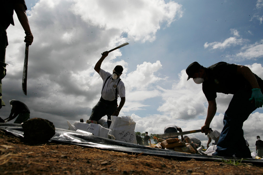 Description of . Anti-narcotics police officers destroy confiscated drugs before incinerating the drugs in Panama City November 23, 2012. More than 10,976,71kg (24,199,50 lbs) of different types of drugs were destroyed by Panama's anti-narcotics police, including some 10,779 kg (23,763 lbs) of cocaine, 109 kg (240 lbs) of marijuana and 58 kg (127 lbs) of heroin. The drugs were seized as part of various police operations around the country from August 22 to November 22, 2012, according to the police. REUTERS/Carlos Jasso
