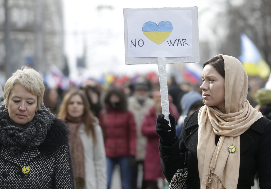 . A Russian woman holds a poster during an anti-war rally in protest against the Russian military actions in Ukraine, during a demonstration in Moscow, Russia, 15 March 2014.  EPA/MAXIM SHIPENKOV