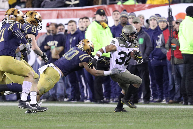 Army running back #32 Artice Hobbs escapes from a tackle attempt by Navy #10 Kevin Brennan.