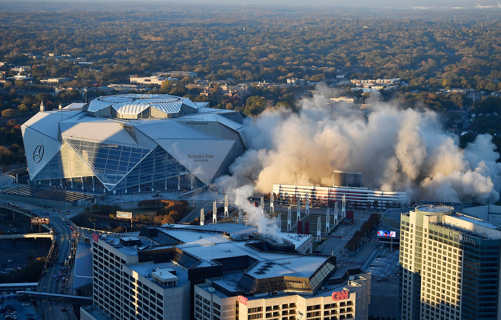 . The Georgia Dome is destroyed in a scheduled implosion next to its replacement the Mercedes-Benz Stadium, left, Monday, Nov. 20, 2017, in Atlanta. The dome was not only the former home of the Atlanta Falcons but also the site of two Super Bowls, 1996 Olympics Games events and NCAA basketball tournaments among other major events. (AP Photo/Mike Stewart)
