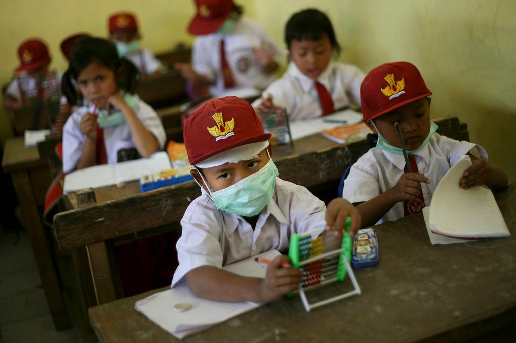 . School children wear masks to protect their respiration from the volcanic ash from the eruption of Mount Sinabung, at an elementary school in Karo, North Sumatra, Indonesia, Tuesday, Sept. 17, 2013. Thousands of people were evacuated from their villages following the eruption of the 2,600-meter (8,530-feet) volcano Sunday after being dormant for three years, sending thick ash into the sky with small rocks pelting neighboring villages. (AP Photo/Binsar Bakkara)