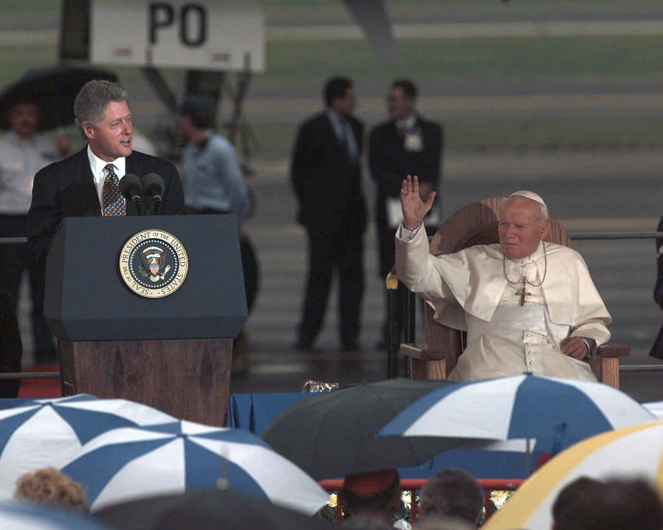 . Pope John Paul II listens as President Bill Clinton addresses the crowd greeting him at Newark International Airport Wednesday Oct. 4, 1995. The Pope is in the United States for a five-day visit. The Pope waved to acknowledge the children who had come out to greet him.  (AP Photo/Charles Rex Arbogast)