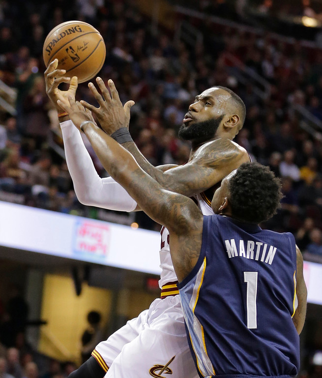 . Cleveland Cavaliers\' LeBron James is fouled by Memphis Grizzlies\' Jarell Martin (1) in the first half of an NBA basketball game Tuesday, Dec. 13, 2016, in Cleveland. (AP Photo/Tony Dejak)