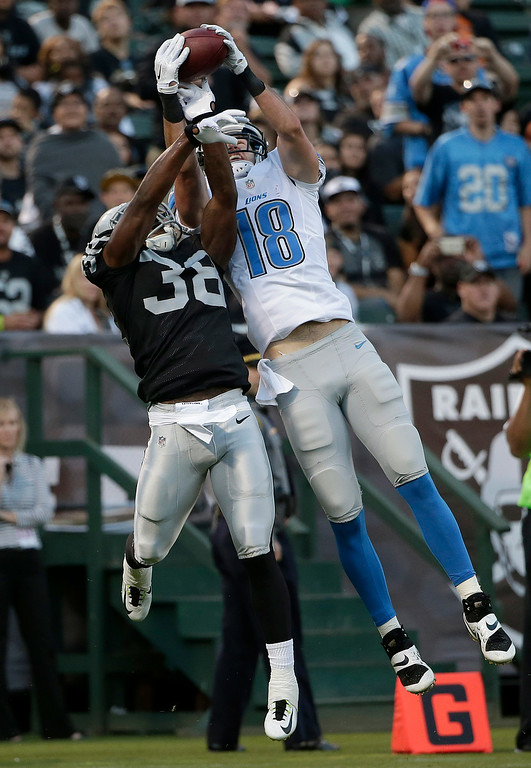 . Detroit Lions wide receiver Kris Durham (18) catches a 4-yard touchdown over Oakland Raiders cornerback T.J. Carrie (38) during the first quarter of an NFL preseason football game in Oakland, Calif., Friday, Aug. 15, 2014. (AP Photo/Marcio Jose Sanchez)