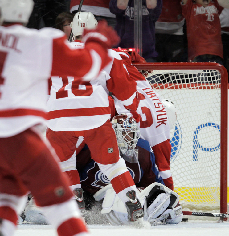 . Detroit Red Wings center Pavel Datsyuk (13) falls on top of Colorado Avalanche goalie Jean-Sebastien Giguere (35) after Datsyuk scored the game-winning goal in overtime of an NHL hockey game Friday, April 5, 2013, in Denver. Detroit won 3-2. (AP Photo/Joe Mahoney)