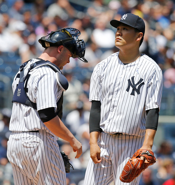 . New York Yankees catcher Brian McCann, left, joints starting pitcher Masahiro Tanaka on the mound as Tanaka reacts after allowing a second-inning, two-run, single to Detroit Tigers designated hitter Victor Martinez in a baseball game at Yankee Stadium in New York, Sunday, June 21, 2015. (AP Photo/Kathy Willens)